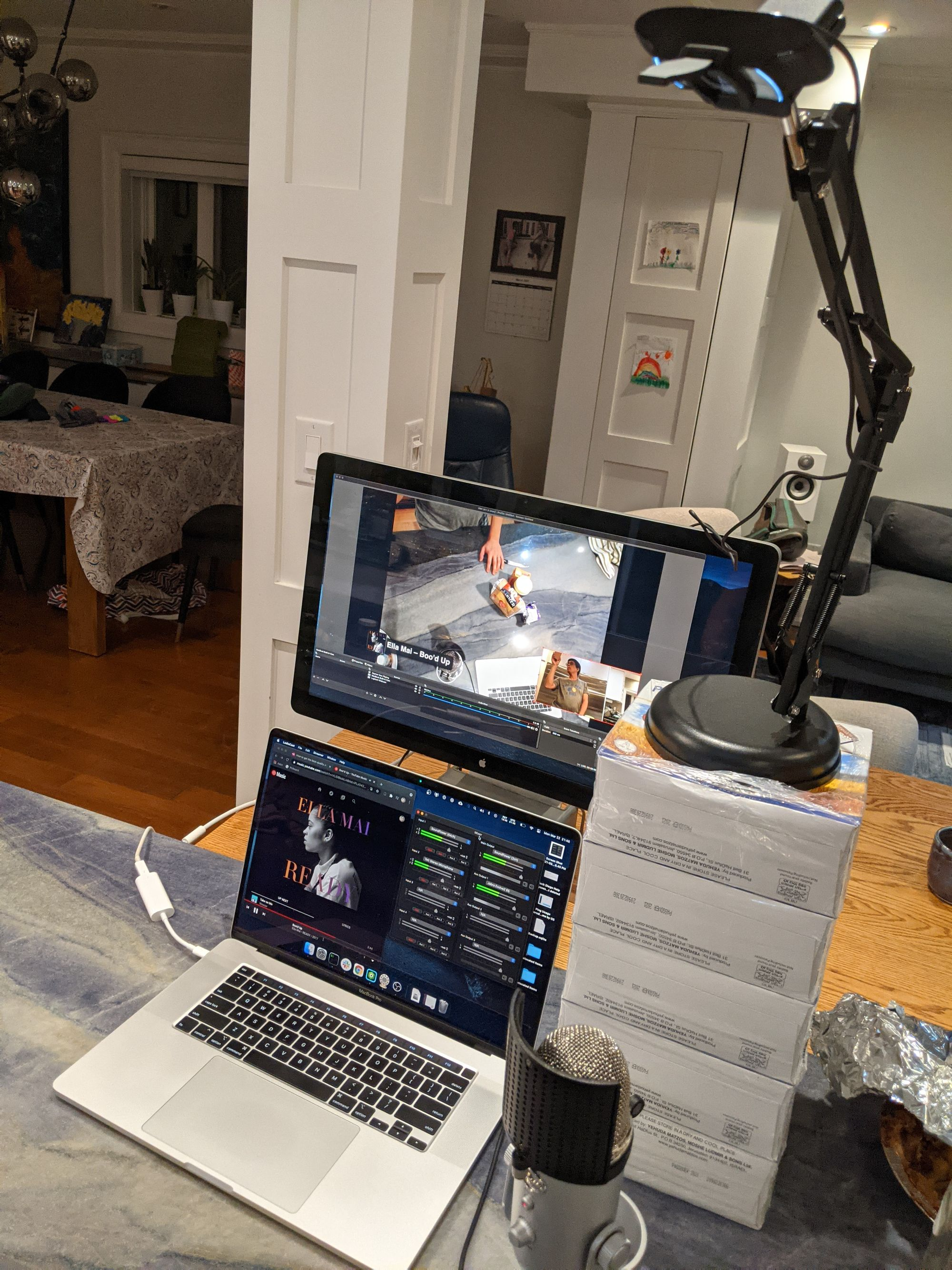 My kitchen island setup: laptop, external monitor, microphone, webcam on a stack of boxes